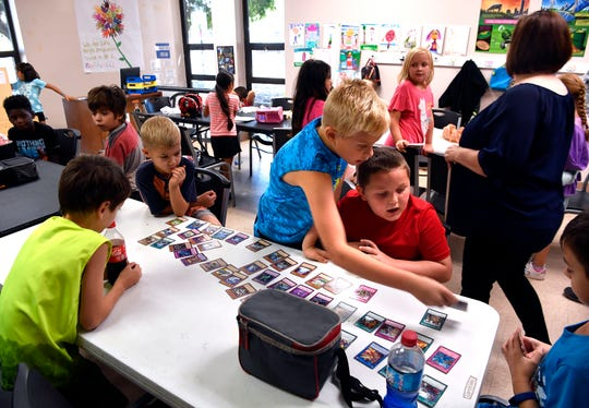 Ethan Butler (in blue) and Braxton Spivey play a card game with other third-graders Friday at the Redbud Park YMCA.