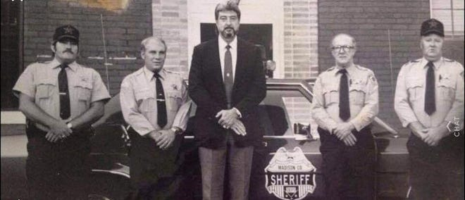 """Known for his imposing stature, James """"Dedrick"""" Brown stands beside deputies outside the old Madison County Jail in downtown Marshall."""