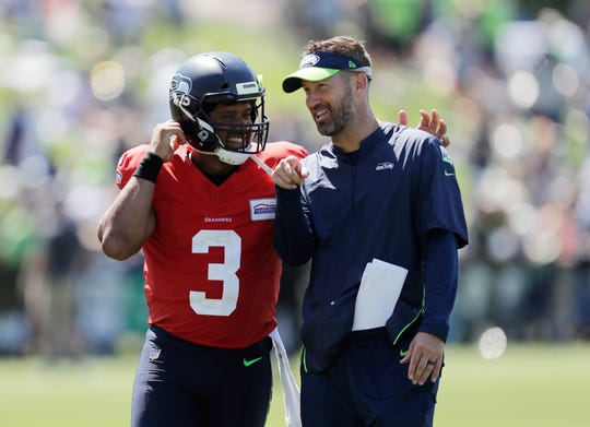 Seahawks quarterback Russell Wilson talks with offensive coordinator Brian Schottenheimer following a training camp practice in Renton. Schottenheimer's plan for Seattle's 2019 offense includes more passing and an optimism that the Seahawks will be more dynamic.