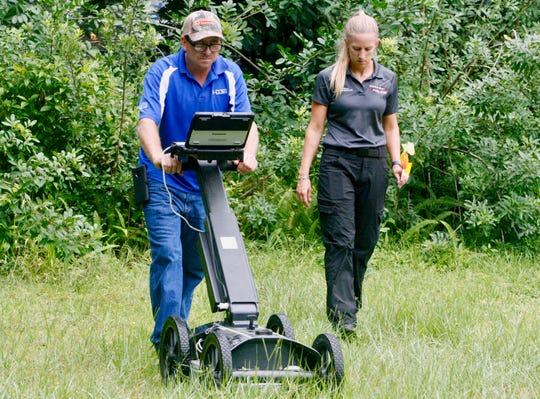 Hugh Ellis, field supervisor for Y-COM uses ground-penetrating radar Friday to try and identify where missing firefighter Brandy Hall's remains might be. Walking alongside him is Palm Bay Police Crime Scene Technician Brittany Paul.