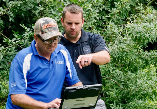 Palm Bay Police Sgt. Jeff Spears (right) goes over ground-penetrating radar data data brought up by Y-COM Field Supervisor Hugh Ellis Friday during a search for Brandy Hall's remains.
