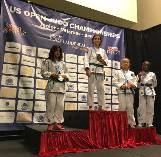 Aubrey Genereux on the medal podium receiving the gold medal in the girls 9-10 year old, 37 kg division.