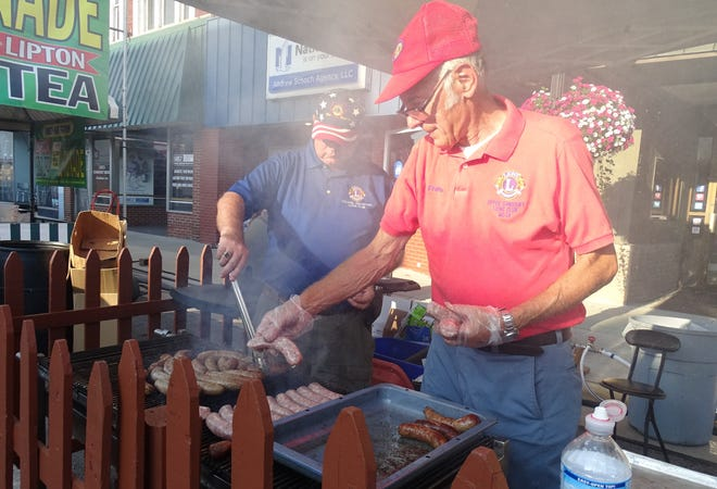 Bratwurst go on the grill at the Lions Club tent during the 2019 Bratwurst Festival.
