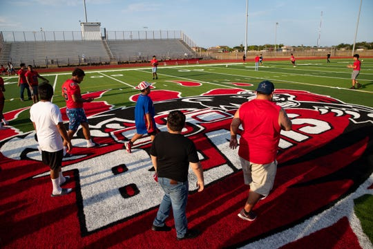 West Oso football players and parents walk the newly turfed field during the schools new football field kickoff on Thursday, Aug. 15, 2019.