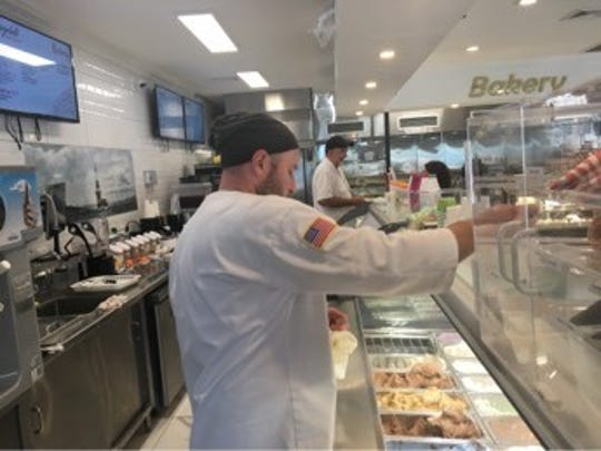 Bagelati owner Zuhtu Kahya dips into some of his gelato flavors to fulfill a customer's order. He makes over 100 flavors at the newly-opened Cinnaminson restaurant.