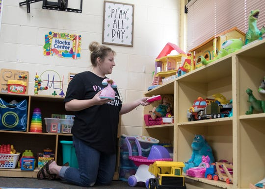 Newly hired preschool teacher Andrea Bolen straightens shelves of toys as she gets ready to receive her students on Monday. Bolen has worked as an aide in pre-K and was previously a computer lab teacher.