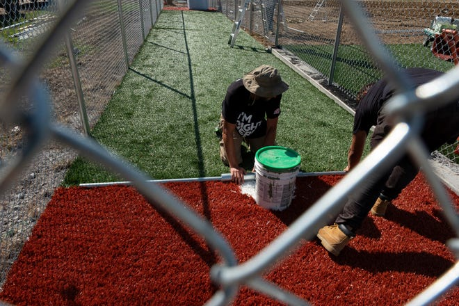 Volunteers lay playing surface at the St. Elizabeth Healthcare Field at the Bellevue Vets Complex in Bellevue, Kentucky on Thursday, August 15, 2019. Over 200 volunteers showed up to help renovate the building as well as adjacent baseball field with help from the Cincinnati Reds, St. Elizabeth Healthcare, the Cincinnati Zoo and Duke Energy as part of the Reds 150th Anniversary of Professional Baseball in 2019.