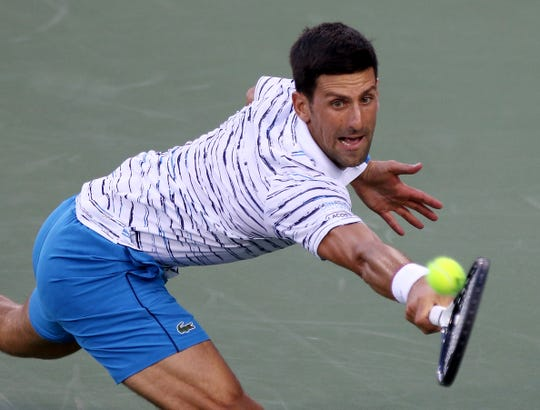 Novak Djokovic stretches to make hit during his match against Pablo Carreno Busta  Thursday, August 15, 2019, at the Western and Southern Open in Mason.