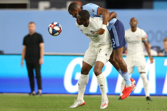 Jun 6, 2019; New York, NY, USA; FC Cincinnati forward Fanendo Adi (9) and New York City FC defender Sebastien Ibeagha (33) fight for the ball during the second half at Yankee Stadium.