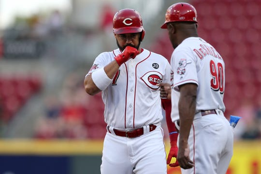 Cincinnati Reds third baseman Eugenio Suarez (7) celebrates a single with Cincinnati Reds first base coach Delino DeShields (90) in the first inning of an MLB baseball game against the St. Louis Cardinals, Thursday, Aug. 15, 2019, at Great American Ball Park in Cincinnati.