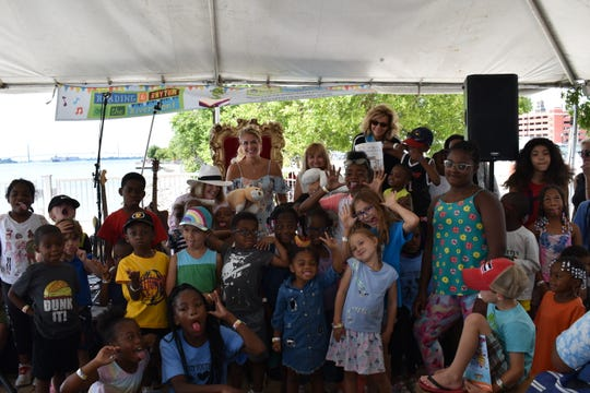 Lori Wingerter (center right)  and author/illustrator Jamie Ruthenberg (center left) were among those who read to the youngsters at the Reading & Rhythm on the Riverfront event Aug. 9 at Cullen Plaza in Detroit.