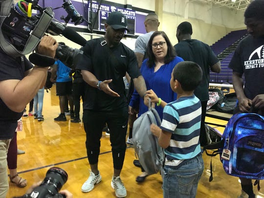 Quandre Diggs gives away a backpack at Angleton high school in Texas, Aug. 14, 2019.