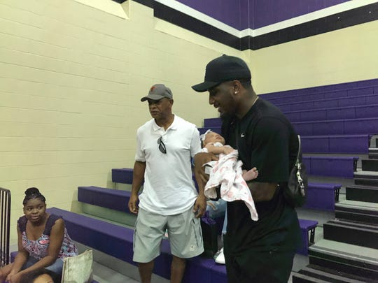 Quandre Diggs with his father and baby daughter at Angleton high school in Texas, Aug. 14, 2019.