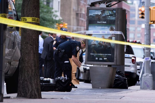 An investigator picks up a suspicious package that was thought to be an explosive device in Manhattan's Chelsea neighborhood Friday in New York.