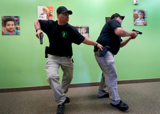 Chris Scott, left, and Charles White, right, slowly walk down a hallway as they clear the area during a security training session at Fellowship of the Parks campus in Haslet, Texas.