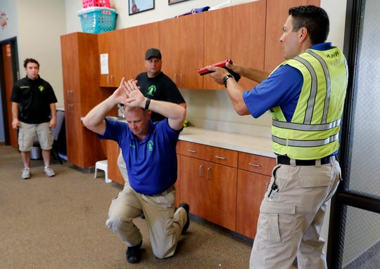 Police officers David Riggall, kneeling, and Nick Guadarrama, right, instruct students Bryan Hetherington, left rear, and Chris Scott, center rear, during a security training session at Fellowship of the Parks campus.