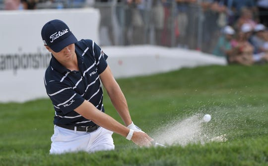 Justin Thomas hits from the bunker on the 18th green.