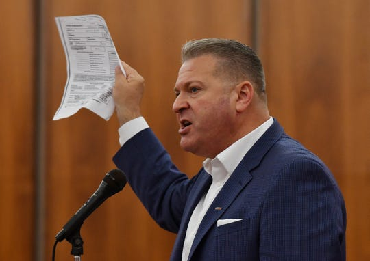 """Oakland County Republican Chair Andrew """"Rocky"""" Raczkowski holds a copy of David Woodward's resignation as he opposes Woodward trying to reclaim his job as board chair after he resigned to compete for the executive's job."""