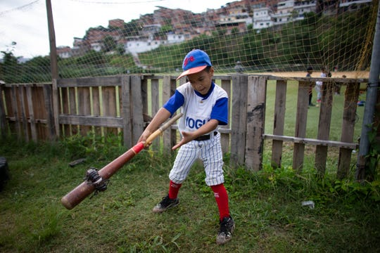 In this Aug. 12 photo, a boy swings a baseball bat using a donut to loosen his muscles during a practice session at the Brisas de Petare Sports Center in Caracas, Venezuela.