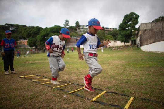 In this Aug. 12 photo, young baseball players perform ladder drills at Las Brisas de Petare Sports Center, in Caracas, Venezuela.