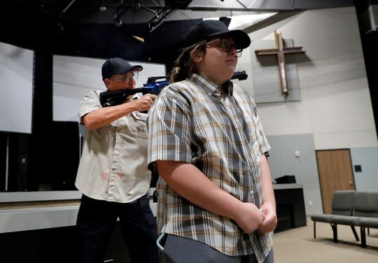 Brett Faulkner, left, fires blanks out of an assault rifle as he and Julia Gant, right, participate in a hostage-taking scenario during a security training session at Fellowship of the Parks campus in Haslet, Texas.