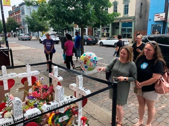 Sabrina Herman, gesturing, visits a makeshift memorial  on Wednesday, Aug. 14, 2019, outside Ned Peppers nightclub in the Oregon District entertainment neighborhood where on Aug. 4 a gunman killed nine people, in Dayton Ohio. Herman, 41, of Dayton, a hospital social worker, visited with her sister, Tara Luikart, right, of Washington Court House.