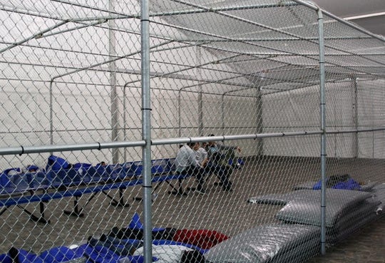 Migrants are detained in a tented, air-conditioned cage at a Border Patrol detention facility in Tornillo, Texas,  Thursday, Aug. 15, 2019. Immigration officials say that with less detainees and more detention space, migrants apprehended along the U.S.-Mexico border won't be subject to the squalid, overcrowded conditions criticized earlier this year.