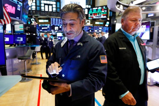 Traders John Romolo, left, and George Ettinger work on the floor of the New York Stock Exchange, Friday, Aug. 16, 2019. Stocks are opening broadly higher at the end of a turbulent week.