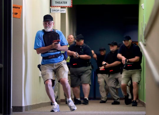 Stephen Hatherley, left, leads fellow trainees down a hallway as they participate in a simulated gun fight scenario at Fellowship of the Parks campus in Haslet, Texas.