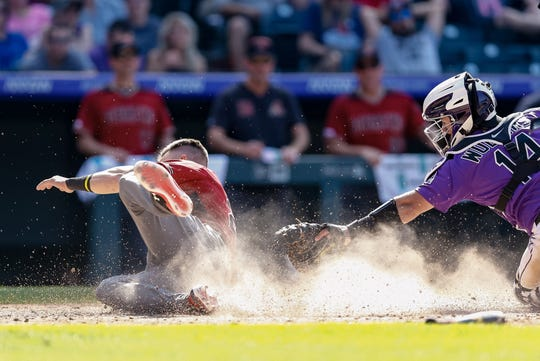 Colorado catcher Tony Walters tries to tag Arizona's Jake Lamb out at home plate during an Aug. 14, 2019, game at Coors Field in Denver. The Rockies are playing home games this weekend against the Miami Marlins at 6:10 p.m. Saturday and 1:10 p.m. Sunday.