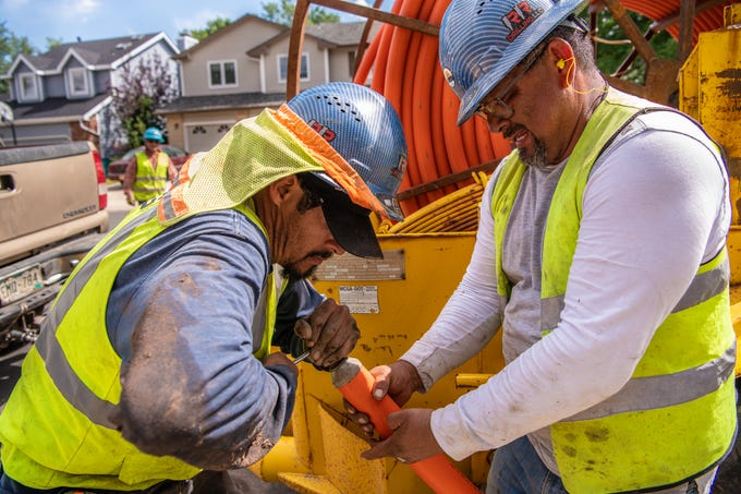Two workers fit an eye bolt into orange conduit before threading it into a recently bored hole on Wednesday, Aug. 14, 2019, in Fort Collins, Colo., at a city construction site for the soon-to-be-launched Fort Collins Connexion fiber network.
