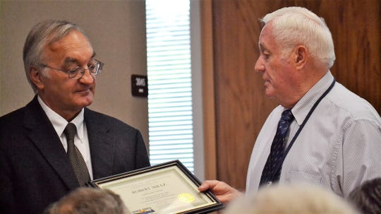 Robert Mraz, left, was recognized in 2013 for 32 years of service as corporation counsel by the Oconto County Board. Handing Mraz a plaque of appreciation was then County Board chair Leland Rymer.