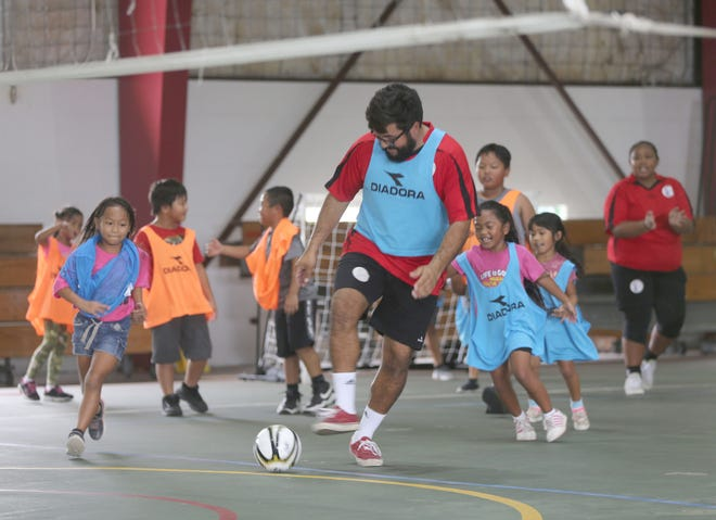 Thomas Castro, a Guam Football Association coach, joins youth players in a futsal game during the pilot futsal program with Haya Youth Center in this file photo from earlier this month at the Agat gym.