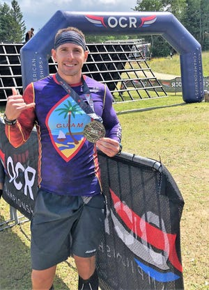 Brian Johnson shows his finisher's medal from the North American OCR Championship held Aug. 10 in Vermont