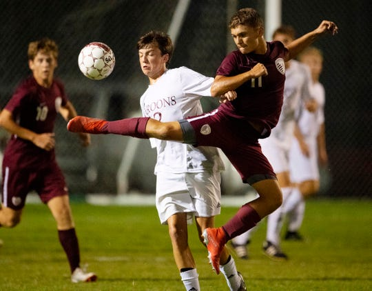 Henderson County's Ashton Todd (11) and Madisonville's Tate Young (12) compete for the ball at Colonel Field Thursday evening. The game ended in a 1-1 tie.