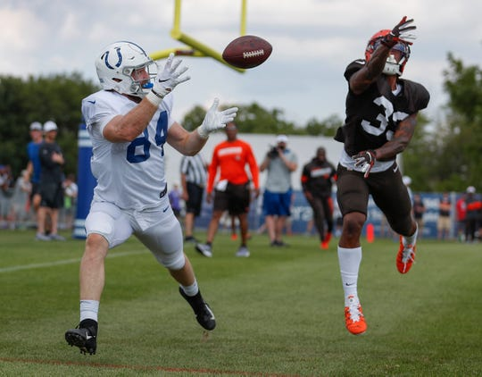 Indianapolis Colts tight end Jack Doyle (84) reaches for the football as Cleveland Browns defensive back Sheldrick Redwine (33) defends during their joint practice at Grand Park in Westfield on Thursday, August 15, 2019.