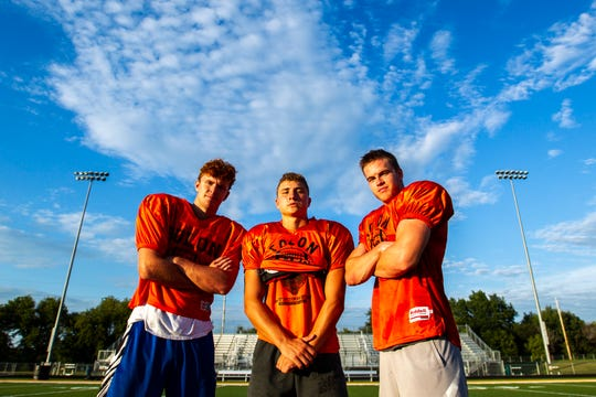 Solon wide receiver A.J. Coons, from left, quarterback Cam Miller, and wide receiver Jace Andregg pose for a photo after a varsity football practice, Thursday, Aug. 15, 2019, at Spartan Stadium in Solon, Iowa.