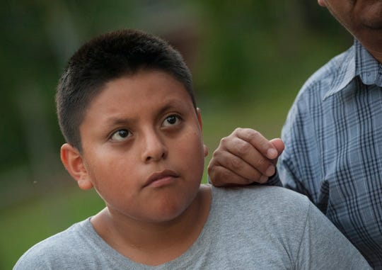 With his father's hand resting on his shoulder, 12-year-old Bryan listens to the conversation about the Wednesday, Aug. 7, 2019, ICE raids in Morton, Miss., and family members who have been detained, including two of Bryan's cousins.