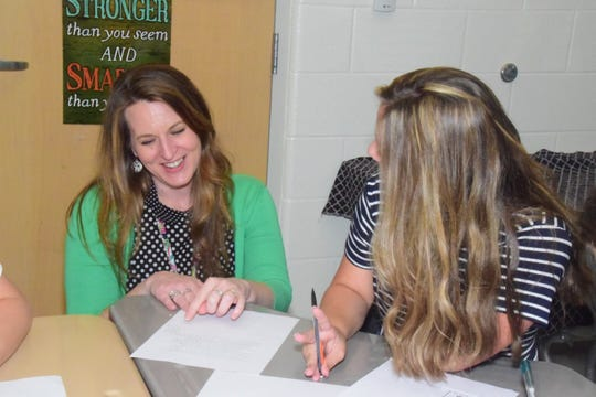 Teacher of the Year Janet Smith helps Hannah Snow, 13, with a writing assignment.