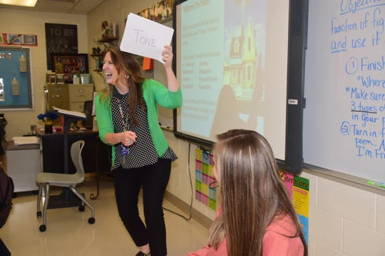 "Janet Smith plays ""Heads Up"" to keep her class engaged at Karns Middle School Thursday, Aug. 15. Smith cracks a smile as Annabelle Ernest, 13, guesses correctly from clues given by the class."