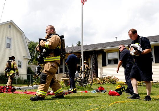 Lancaster firefighters carry two cats away from the scene of a house fire Friday afternoon, Aug. 16, 2019, in the 200 block of Mount Ida Avenue. A fire that started in the kitchen fire damaged most of the home. LFD Capt. Larry Moore said a woman who lives at the house was being observed by medics at the scene but had refused to be taken to the hospital. Firefighters found the woman's four cats inside the house. One died from smoke inhalation. Asst. Chief KJ Watts took the other three cats to Diley Hill Animal Emergency Center in Canal Winchester in one of the fire department's command vehicles.