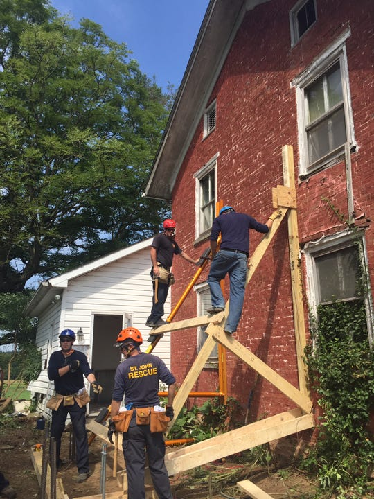 Firefighters in the Bowling Green State University rescue tech program took their final exam in structural collapse at a donated house on Beatty Road in Pleasant Township Thursday. These firefighters are putting a brace on the house.