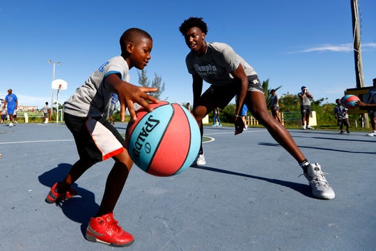 Memphis Tigers center James Wiseman works with kids on their dribbling skills during a basketball clinic for young children at the Bozine Town Community Park in Nassau, Bahamas, on Friday, Aug. 16, 2019.