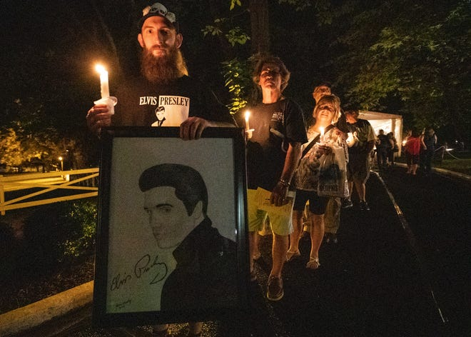 "Elvis Presley fan, Shane greenly, attends a candlelight vigil during ""Elvis Week"" that marks the 42nd anniversary of Presley's Aug. 16 death."