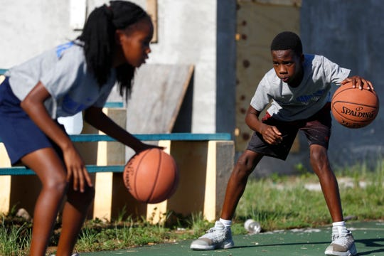 Siblings Raynia, 11, and Raynor Russell, 13, dribble during a Memphis Tigers basketball clinic for young children at the Bozine Town Community Park in Nassau, Bahamas on Friday, August 16, 2019.
