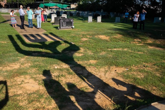 Tyler French's menorah sculpture casts a long shadow as viewers look on Friday morning, August 16, 2019 in Anshei Sphard Cemetery.