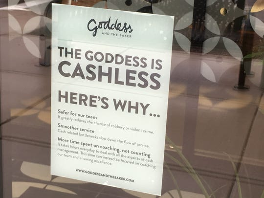 A sign in the window at the Goddess and the Baker explains why the restaurant in the Town of Brookfield doesn't accept cash.