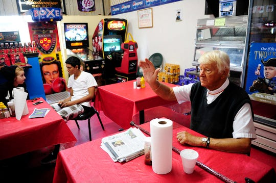 Del Ackerman waves to departing customers as Ashley Poole, 16, left, talks with friend Joseph Torres, 15, who stopped in to warm up Friday, Jan. 3, 2014, at Del's 24 Hour Store in Naples.
