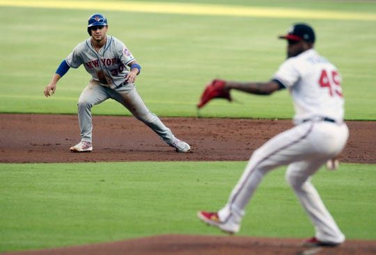 New York Mets Michael Conforto, left, takes a lead off second base as Atlanta Braves pitcher Julio Teheran throws during the first inning of a baseball game Thursday, Aug. 15, 2019, in Atlanta. (AP Photo/Tami Chappell)