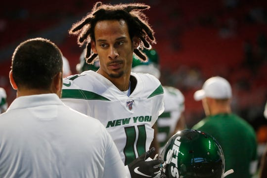 New York Jets wide receiver Robby Anderson (11) speaks with a coach during the first half an NFL preseason football game between the Atlanta Falcons and the New York Jets, Thursday, Aug. 15, 2019, in Atlanta.